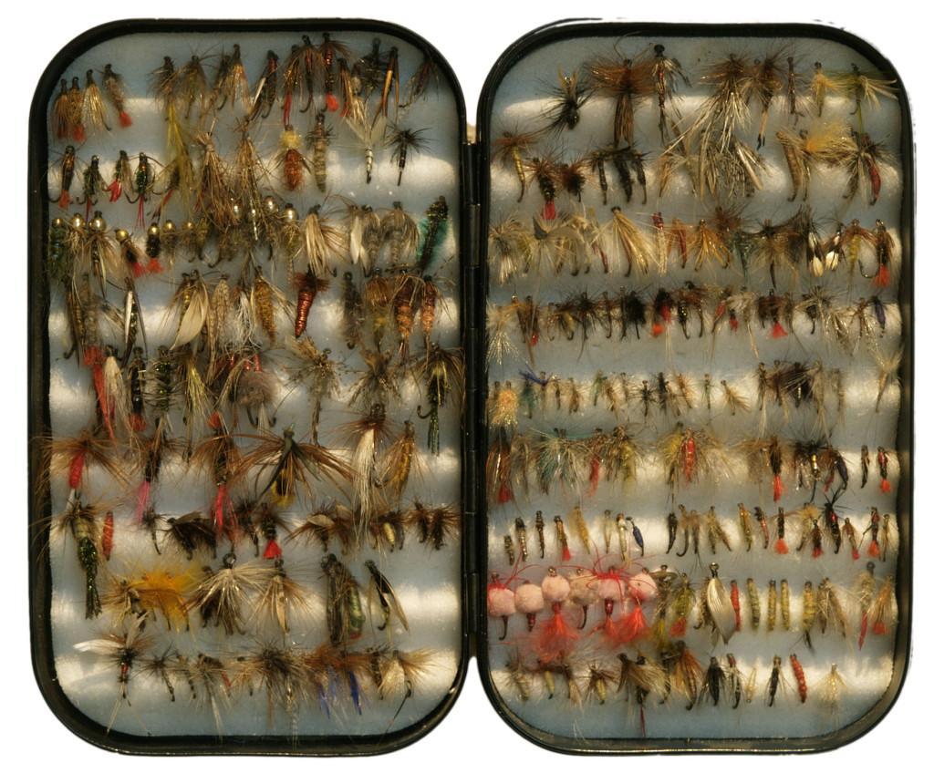 """Der Gegenstand stellt eine Sammlung von Ködern dar, die zum Fliegenfischen verwendet werden; es handelt sich um kleine Angelhacken mit künstlich gefertigten """"Fliegen"""". Diese Angelhacken/Antikörper sollen symbolisch dazu dienen, sich in glattgebügelten (Stoff)Geweben festzuhaken und diese zu entglätten."""