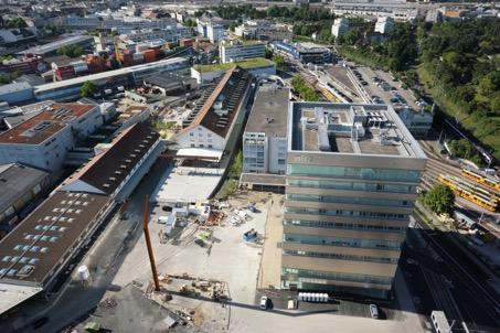 Luftbild Dreispitz-Areal, öffentliche Freiräume zwischen dem Hochhaus und dem umgebauten Zollfreilager als neuer Standort für die Kunsthochschule (HGK Basel)
